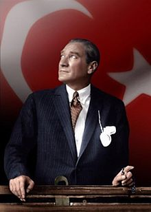 Mustafa_Kemal_Ataturk_looking_through_a_train_window_over_Turkish_flag.jpg
